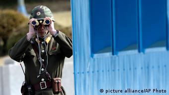 A North Korean soldier looks at the southern side through a pair of binoculars at the border village of the Panmunjom (Photo: AP Photo/Lee Jin-man)