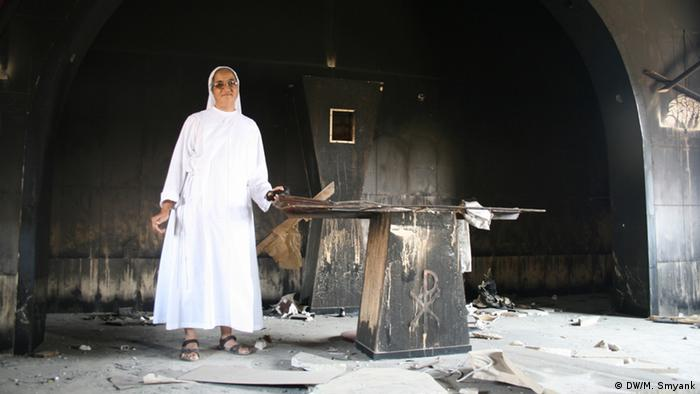 Standing next to a charred alter, the white robes of a nun of Middle Eastern descent contrast strikingly with the black, burned-out shell of a former Franciscan school. (Photo: Markus Symank / DW)