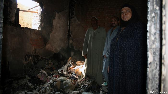 A Middle Eastern family wearing robes stands in the darkened and rubble-filled room of their destroyed former house.