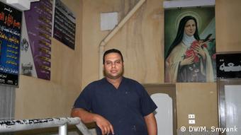 Standing next to a picture of the Virgin Mary affixed to the wall, a man of Middle Eastern descent wearing a blue, short-sleeved collared shirt rests his arm on a metal rail in a beige room. (Photo: Markus Symank / DW)