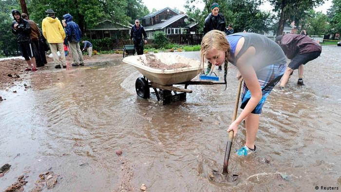 Malia Clearwater shovels debris into a dike to funnel to funnel water down a street as heavy rains cause severe flooding in Boulder, Colorado September 12, 2013. Flash flooding caused by torrential downpours in Colorado has killed at least three people and forced hundreds to flee to higher ground as rising water caused buildings to collapse and stranded cars, officials said on Thursday. REUTERS/Mark Leffingwell (UNITED STATES - Tags: DISASTER ENVIRONMENT)