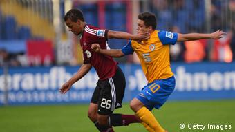 Timothy Chandler of Nuernberg is challenged by Mirko Boland of Braunschweig