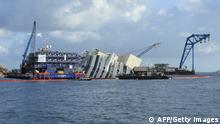Members of the US salvage company Titan and Italian firm Micoperi work at the wreck of Italy's Costa Concordia cruise ship near the harbour of Giglio Porto on September 16, 2013. Salvage workers will attempt to raise the cruise ship today, in the largest and most expensive maritime salvage operation in history, so-called parbuckling, to rotated the ship by a series of cables and hydraulic machines. Thirty-two people died when the ship, with 4,200 passengers onboard, hit rocks and ran aground off the island of Giglio on January 2012. AFP PHOTO / ANDREAS SOLARO (Photo credit should read ANDREAS SOLARO/AFP/Getty Images)