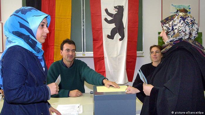 Berlin: Zwei türkische Frauen mit Kopftüchern stehen am 21.10.2001 an der Wahlurne in einem Wahllokal im Berliner Bezirk Kreuzberg. Nach der Aufkündigung der großen Koalition wurden die Berliner vorzeitig zu Neuwahlen aufgerufen. (BER18-211001)