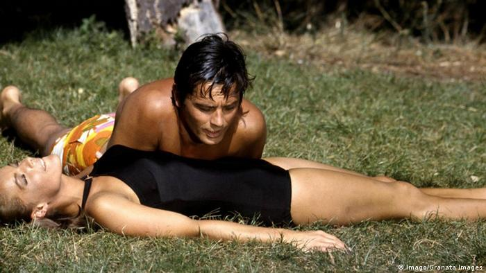 Romy Schneider und Alain Delon liegen in Badekleidung auf einer Wiese im Film Der Swimmingpool. (Imago/Granata Images)