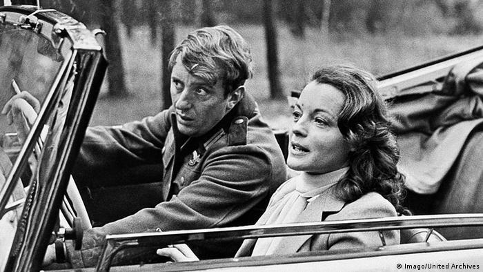 Vadim Glowna und Romy Schneider sitzen in einem Cabrio im Film Gruppenbild mit Dame. (Imago/United Archives)