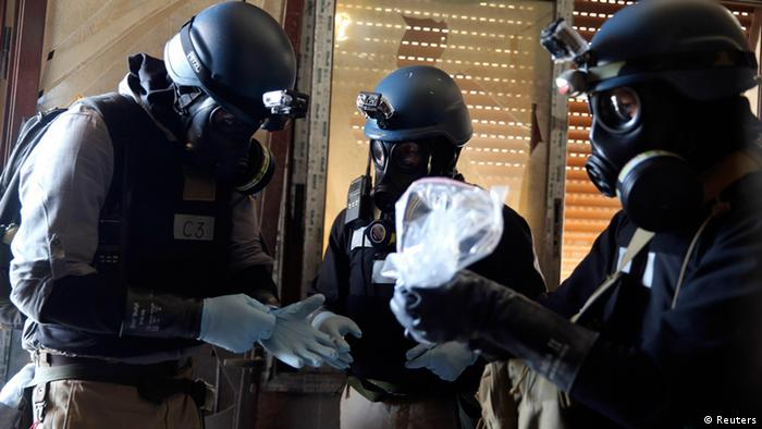 A UN chemical weapons expert, wearing a gas mask, holds a plastic bag containing samples from one of the sites of an alleged chemical weapons attack in the Ain Tarma neighbourhood of Damascus in this August 29, 2013 file photo. (Photo: REUTERS/Mohamed Abdullah/Files)
