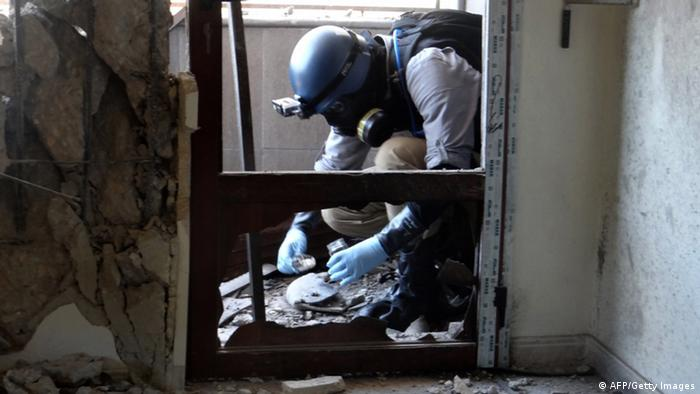 A United Nations (UN) arms expert collects samples on August 29, 2013, as they inspect the site where rockets had fallen in Damascus' eastern Ghouta suburb during an investigation (AFP/Getty Images)