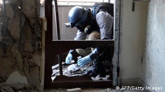 Инспектор ООН берет пробы газа после атаки в Гуте в 2013 году