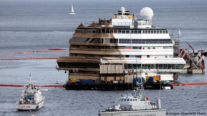 The Costa Concordia is seen after it was lifted upright on the Tuscan Island of Giglio, Italy, early Tuesday morning, Sept. 17, 2013. The crippled cruise ship was pulled completely upright early Tuesday after a complicated, 19-hour operation to wrench it from its side where it capsized last year off Tuscany, with officials declaring it a perfect end to a daring and unprecedented engineering feat. (AP Photo/Andrew Medichini)