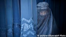 FILE - In this Thursday, April 11, 2013 file photo, an Afghan woman peers through the the eye slit of her burqa as she waits to try on a new burqa in shop in the old town of Kabul, Afghanistan. Conservative religious lawmakers in Afghanistan blocked a law on Saturday, May 18, 2013 that aims to protect women's freedoms, with some arguing that parts of it violate Islamic principles or encourage women to have sex outside of marriage. (AP Photo/Anja Niedringhaus, File)
