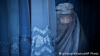In this Thursday, April 11, 2013 file photo, an Afghan woman peers through the the eye slit of her burqa as she waits to try on a new burqa in shop in the old town of Kabul, Afghanistan. (Photo: AP Photo/Anja Niedringhaus, File)