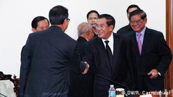 16 September 2013: Cambodia's Prime Minister Hun Sen (centre, with glasses) shakes the hand of opposition leader Sam Rainsy during their meeting at parliament. (Photo: DW/ Robert Carmichael)
