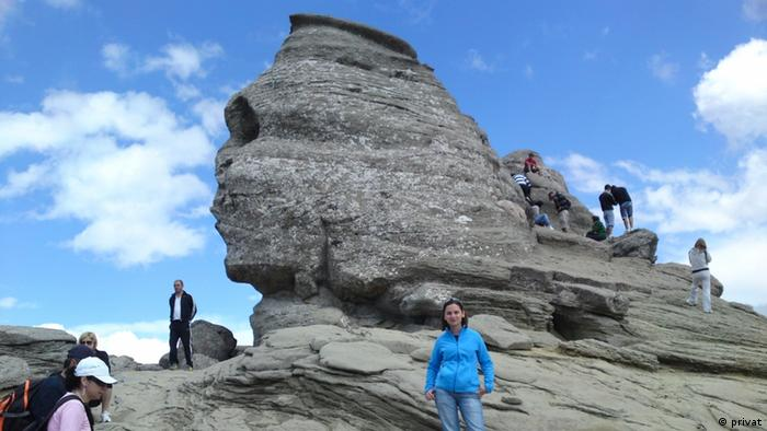 Georgiana in front of the Bucegi-Sphinx, one of three rock formations in the Bucegi-Massif, located in the southern Carpathian Mountains.