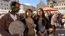 Eric, Almudena und Nichole stehen mit Blumenkränzen im Haar auf einem Töpfermarkt und Eric hält einen getöpferten Teller in der Hand.
