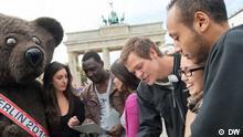 Die sechs Kandidaten stehen mit dem Berliner Bären vorm Brandenburger Tor.