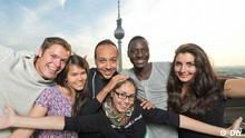 Die sechs Kandidaten lachen in die Kamera. Im Hintergrund ist der Berliner Fernsehtum zu sehen.