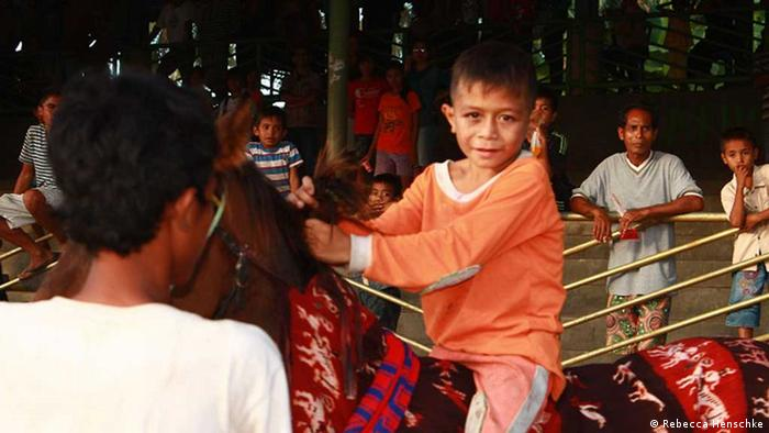 A young Indonesian boy wearing orange clothing rides a horse in Indonesia Foto: Rebecca Henschke