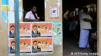 A Sri Lankan man stands near election posters in Jaffna, 400 kilometres (250 miles) north of the capital Colombo on September 18, 2013. Sri Lanka is holding the first ever provincial council election, scheduled for September 21. AFP PHOTO/LAKRUWAN WANNIARACHCHI (Photo credit should read LAKRUWAN WANNIARACHCHI/AFP/Getty Images)