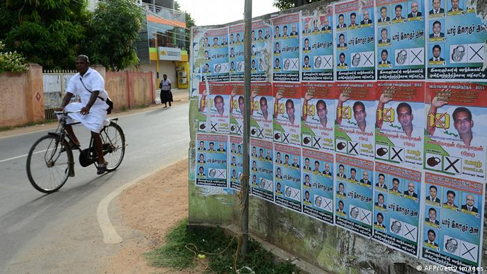 A Sri Lankan man rides his bicycle past election posters in Jaffna, 400 kilometres (250 miles) north of the capital Colombo on September 18, 2013. Sri Lanka is holding the first ever provincial council election, scheduled for September 21. AFP PHOTO/LAKRUWAN WANNIARACHCHI (Photo credit should read LAKRUWAN WANNIARACHCHI/AFP/Getty Images)