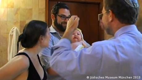Bild aus dem Film Baby Conversion to Judaism, Regie: Jennifer Kaplan, USA 2010. Der Film ist Teil der Ausstellung Treten Sie aus! Treten Sie ein!, die im Jüdischen Museum München ab 1. Oktober 2013 gezeigt wird. - Copyright: Jüdisches Museum München 2013