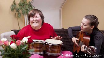 Eine Therapeutin mit Gitarre und eine Patientin mit Bongos machen Musik (Foto: Miriam Dörr)