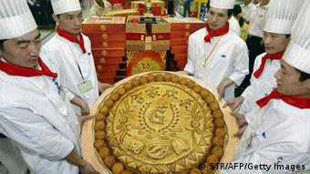 BEIJING, CHINA: A group of Chinese chefs show off their creation, a giant mooncake, for the upcoming mid-autumn festival, in Beijing 14 September 2004. The giant mooncake will be the main attraction for the annual festival, which will fall on 28 September. AFP PHOTO (Photo credit should read STR/AFP/Getty Images)