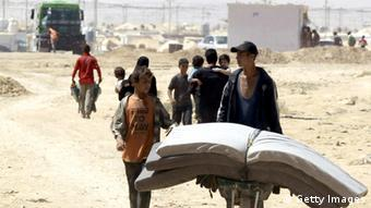 Young Syrian refugees transport mattresses through the Zaatari refugee camp KHALIL MAZRAAWI/AFP/Getty Images)