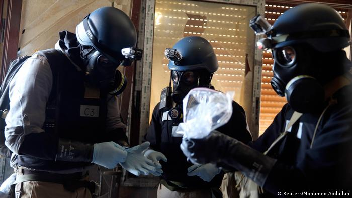A U.N. chemical weapons expert, wearing a gas mask, holds a plastic bag containing samples from one of the sites of an alleged chemical weapons attack in the Ain Tarma neighbourhood of Damascus in this August 29, 2013 file photo. A report by U.N. chemical weapons experts will likely confirm that poison gas was used in an August 21 attack on Damascus suburbs that killed hundreds of people, U.N. Secretary-General Ban Ki-moon said on September 13, 2013. France's U.N. ambassador, Gerard Araud, told reporters that September 16, 2013 is the tentative date for Ban to present Sellstrom's report to the Security Council and other U.N. member states. REUTERS/Mohamed Abdullah/Files (SYRIA - Tags: POLITICS CIVIL UNREST CONFLICT HEALTH)