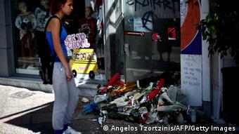 A woman stands on September 19, 2103 in front of the spot where was murdered Pavlos Fyssas, in Piraeus, Greece. Pavlos Fyssas, a 34-year-old left-wing hip hop singer, was stabbed to death early morning on 18 Sept. 2013 outside a Keratsini cafeteria. Police said a 45-year-old alleged member of the Golden Dawn neo-Nazi group arrested at the scene of the killing. AFP PHOTO / ANGELOS TZORTZINIS (Photo credit should read ANGELOS TZORTZINIS/AFP/Getty Images)