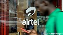 TO GO WITH AFP STORY BY OTTO BAKANO A man with his phone in hand walks past a window branded in an 'Airtel' logo on May 20, 2011 in the Kenyan capital, Nairobi. India will seek to expand its economic footprint in Africa, where its rival China has made major inroads, at the second India-Africa summit next week in Addis Ababa. India's Bharti Airtel -- the world's fifth largest mobile phone company -- acquired the 16-African country unit of Kuwaiti telecom firm, Zain at a cost of $10.7 billion in 2010 when India's imports from Africa were worth $20.7 billion and its exports stood at $10.3 the same year even though China's trade with Africa remains far heftier. AFP PHOTO/Tony KARUMBA (Photo credit should read TONY KARUMBA/AFP/Getty Images)