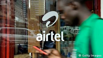 A man with his phone in hand walks past a window branded in an 'Airtel' logo in the Kenyan capital, Nairobi.
