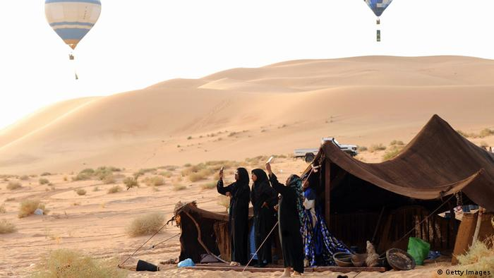 Tuaregs take photos of hot air balloons with their cell phones