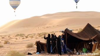 Women photographing balloons with their mobile phones, standing in from of their tents in a desert.