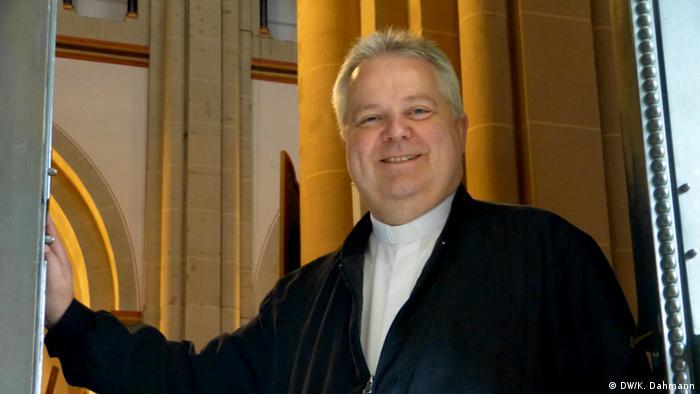Der Bonner Pfarrer Thomas Bernards öffnet die Pforte zur Münsterkirche in der Bonner Innenstadt. -  Foto: Klaus Dahmann, DW