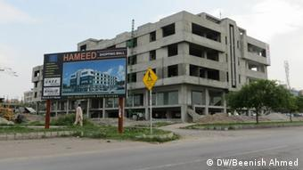 "A multi-story which building is under construction along a road. In front of it stands a sign that reads ""Hameed Shopping Centre."""