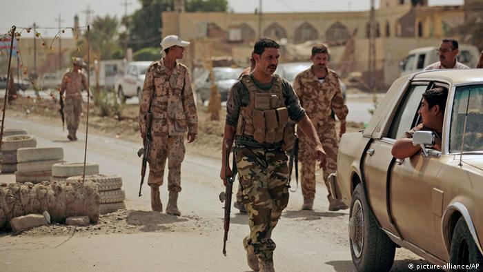 FILE - In this Monday, Oct. 6, 2010, file photo, armed Sunni militiamen work at a checkpoint in Samarra, 60 miles (95 kilometers) north of Baghdad, Iraq. Two bombs hidden inside air conditioners exploded Friday, Sept. 20, 2013, in a Sunni mosque packed with worshippers north of Baghdad, killing at least a dozen people in the latest in a string of attacks on the sect's holy sites in Iraq. (AP Photo/Maya Alleruzzo, File)