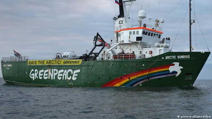 A large green ship floating in dark ocean water has a brightly-colored rainbow streaking up its bow into the shape of a dove.