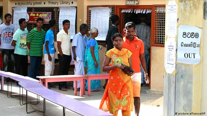 A Sri Lankan ethnic Tamil couple leaves after casting their vote as others line up to vote at a polling station during (AP Photo/Eranga Jayawardena)