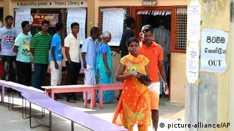 A Sri Lankan ethnic Tamil couple leaves after casting their vote as others line up to vote at a polling station during the northern provincial council election in Jaffna, Sri Lanka, Saturday, Sept. 21, 2013.