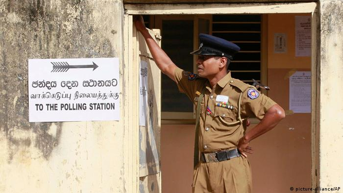 A Sri Lankan police officer stands guard at a polling station during the northern provincial council election in Jaffna, Sri Lanka, Saturday, Sept. 21, 2013. (Photo: AP)