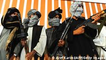 Former Taliban fighters stand with their weapons during a ceremony after joining Afghan government forces in Herat on August 7, 2013. About 100,000 foreign combat troops, 68,000 of them from the US, are due to exit by the end of 2014, and NATO formally transferred responsibility for nationwide security to Afghan forces a week ago. AFP PHOTO/ Aref Karimi (Photo credit should read Aref Karimi/AFP/Getty Images)