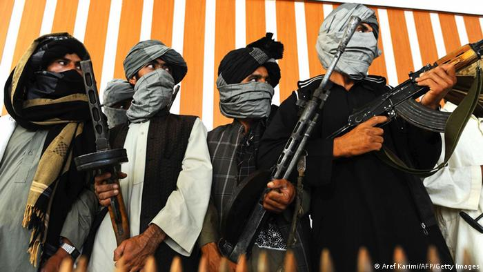 Former Taliban fighters stand with their weapons during a ceremony after joining Afghan government forces in Herat on August 7, 2013 (Photo: Aref Karimi/AFP/Getty Images)