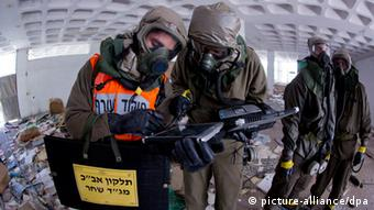 epa03721207 A team from a special unit in the Israeli Home Front Command, which tests an area for any traces of nuclear or biological or gas contamination, use a computer as they wear full protective suits in Holon, outside Tel Aviv, Israel, 28 May 2018 during a drill testing Israel's preparedness for an unconventional weapons attack. The scenario is part of a nation wide three day drill called 'Turning Point 7' to test how the country is prepared for unconventional weapons attacks. EPA/JIM HOLLANDER