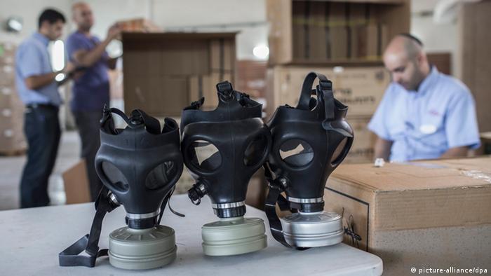 Eine Stelle in Tel-Aviv, an der Gasmasken an die Bevölkerung verteilt werden; im Vordergrund Gasmasken, im Hintergrund Mitarbeiter mit Kippa - Foto: Oliver Weiken (EPA)