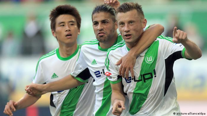 Wolfsburg striker Ivica Olic (right) celebrates the first of his two goals in his side's 2-1 win over Hoffenheim with team-mates Koo Ja-Cheol (left) and Ricardo Rodriguez (centre). Olic's double takes his tally to the season to four, and also moves Wolfsburg up to sixth on the table. Photo: dpa