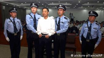 In this photo released by the Jinan Intermediate People's Court, fallen politician Bo Xilai, center, is handcuffed and held by police officers as he stands at the court in Jinan, in eastern China's Shandong province Sunday, Sept. 22, 2013. The Chinese court convicted Bo on charges of taking bribes, embezzlement and abuse of power and sentenced him to life in prison, capping one of the country's most lurid political scandals in decades. (AP Photo/Jinan Intermediate People's Court) ***FREI FÜR SOCIAL MEDIA***