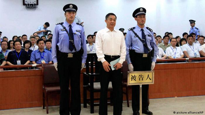 In this photo released by the Jinan Intermediate People's Court, Bo Xilai, center, who was tried last month on charges of taking bribes, embezzlement and abuse of power, stands inside the court in Jinan, in eastern China's Shandong province, Sunday, Sept. 22, 2013. The Chinese court convicted the fallen politician of corruption and sentenced him to life in prison. (AP Photo/Jinan Intermediate People's Court) ***FREI FÜR SOCIAL MEDIA***