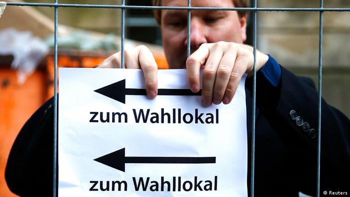 Bundestagswahl Deutschland 22.09.2013 Wahllokal: Ein Wahlhelfer hängt einen hinweis auf. (Foto: dpa)
