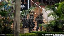 Soldiers from the Kenya Defense Forces carry a wounded colleague, following the sound of explosions and gunfire, out of the Westgate Mall in Nairobi, Kenya Sunday, Sept. 22, 2013. Associated Press journalists at the scene of a hostage standoff said a barrage of gunfire erupted from the upscale Kenyan mall Sunday morning and moments later two wounded Kenyan security forces were carried out of the mall. (AP Photo/Ben Curtis) ***FREI FÜR SOCIAL MEDIA***